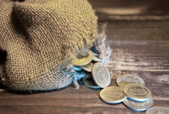 Münzen fallen aus Geldsack durch Loch
